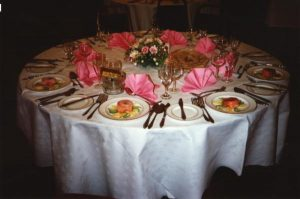 Circular table beautifully laid with pink fanned napkins and the first course.